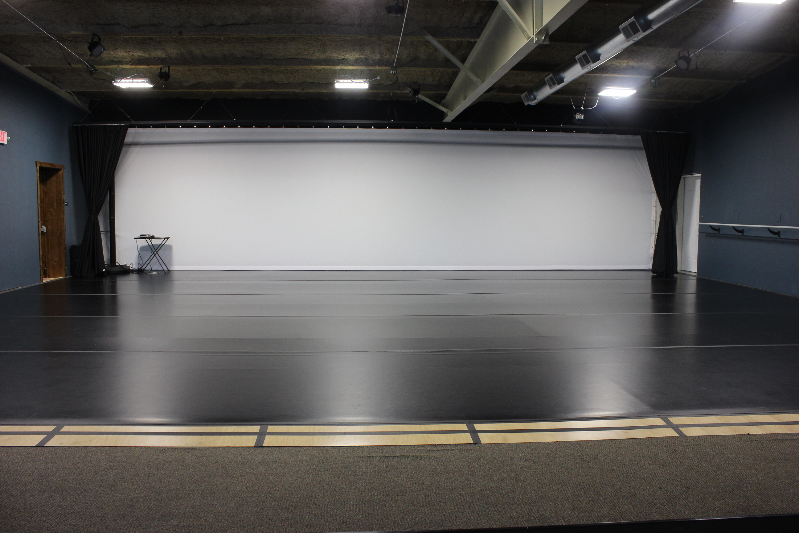 A large dance studio pictured with black marley flooring and a white cyc. A sound system sits in the corner.