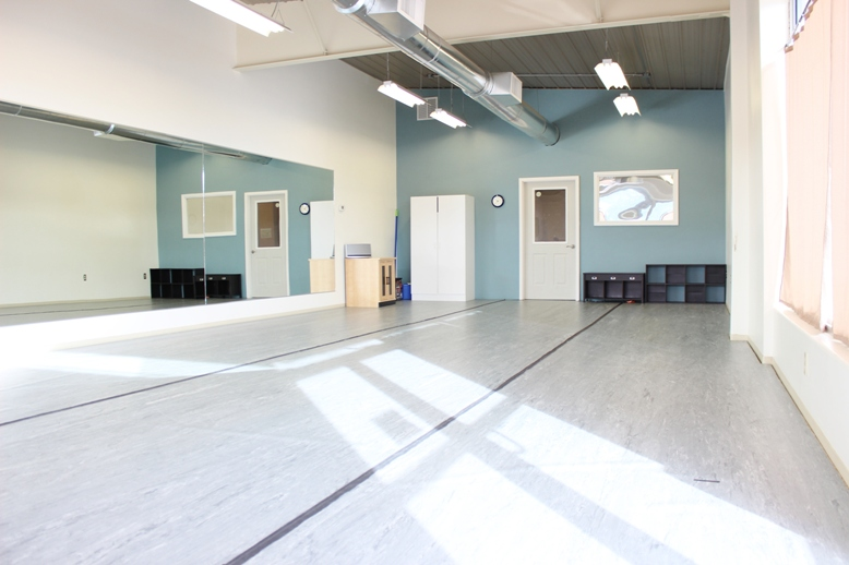 A dance studio with grey marley flooring showing full length mirrors and a sun beam on the floor.